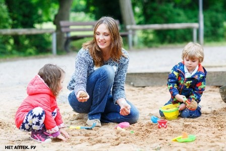 Happy mother and two little children playing together on playground in summer